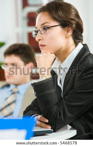 Portrait of  thoughtful businesswoman with glasses putting  her chin on the fist