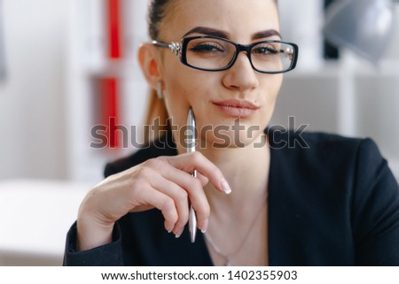 Portrait of thoughtful female looking at camera coquettishly and cheerfully. Attractive girl touching tender cheek with iron ball-pen. Way to success concept. Blurred background