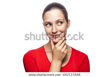 Portrait of thoughtful happy woman in red t-shirt with freckles, studio shot. isolated on white background.