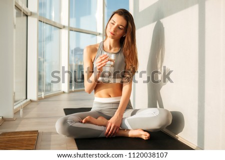 Portrait of thoughtful lady in sporty top and leggings sitting in lotus pose on yoga mat and drinking pure water at home with big beautiful windows on background #1120038107