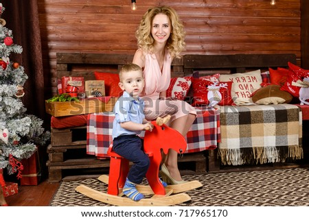 Portrait of thoughtful little boy swinging on a wooden horse in the decorated room. On the background mother sitting on a sofa with blanket and pillows. Concept of Merry Christmas and Happy New Year #717965170