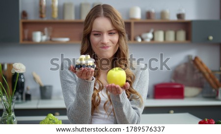 Portrait of thoughtful woman choosing between healthy food and unhealthy food in kitchen. Closeup of smiling girl looking at dessert and apple indoors. Emotional woman preferring fresh fruit Photo stock ©