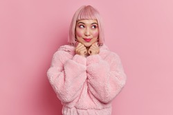 Portrait of thoughtful young Asian woman keeps hands under chin has dreamy expression bright makeup pink bob hairstyle wears fur coat thinks how to spend weekend. People fashion style concept