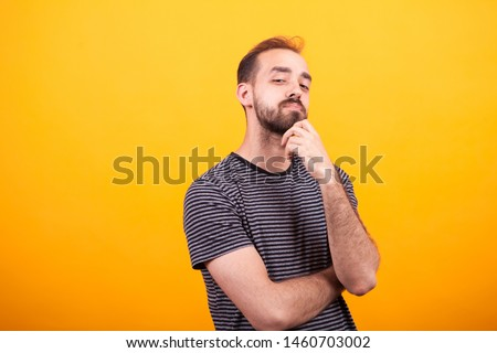 Portrait of thoughtful young man looking into the camera looking at the camera over yellow background. #1460703002