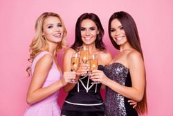 Portrait of three amazing, cute, pretty, astonished girls in luxury short dresses holding glasses with champagne, spending  together new year party, standing over pink background