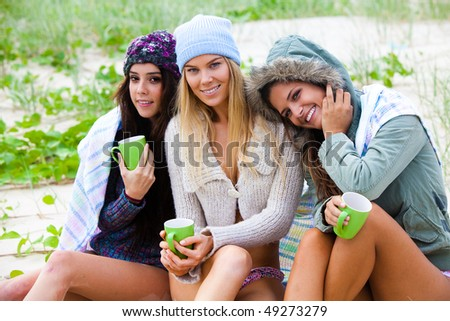 Portrait of three attractive young women smiling and sitting together on a beach.  They are bundled up against the chilly weather and are holding green coffee cups. Horizontal shot.