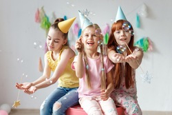 Portrait of three beautiful girls wear festive caps, play with bubbles, sit together on chair, celebrate birthday, being in good mood, use magic wand, have party in decorated room. Childhood concept