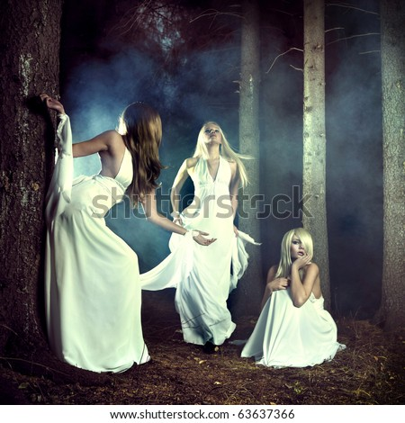Portrait of three beautiful nymphs in misty forest