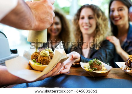 Portrait of three beautiful young women buying meatballs on a food truck in the park.