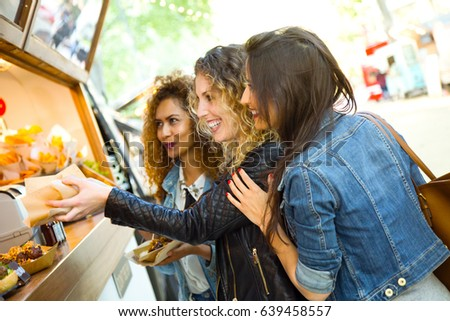 Portrait of three beautiful young women visiting eat market in the street.