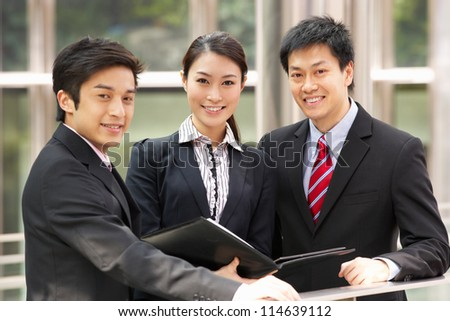 Portrait Of Three Business Colleagues Discussing Document Outside Office