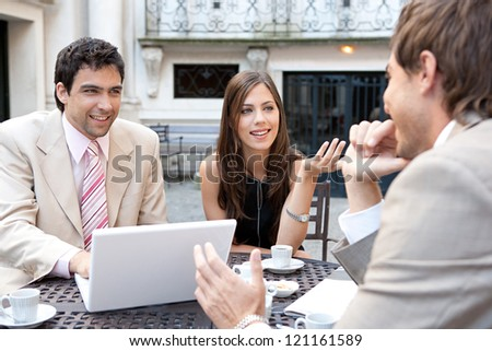 Portrait of three business people sharing a table at a coffee shop terrace, having a meeting and talking while using technology in the financial city district.