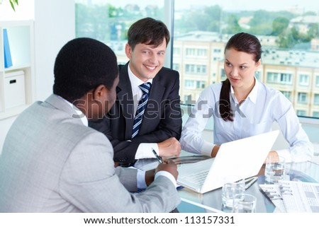 Portrait of three businesspeople interacting in office