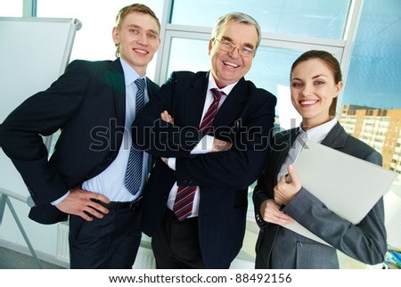 Portrait of three businesspeople looking at camera and smiling