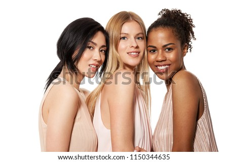 Portrait of three cheerful multinational young female with attractive appearance and different flawless skintone. Diverse friends concept. Isolated on white background