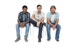 Portrait of three cool young men sitting on chairs over white background