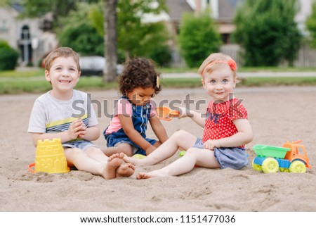 Portrait of three cute Caucasian and hispanic latin toddlers babies children sitting in sandbox playing with plastic colorful toys. Little girls and boy friends having fun together on playground.