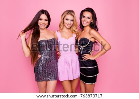 Portrait of three cute, nice best girlfriends, hugging each other on waist, posing for photo on someone's birthday bachelor evening party, standing over pink background