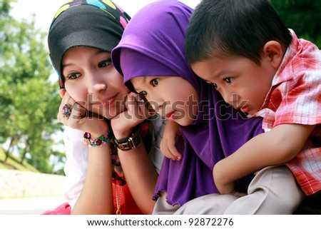 Portrait of three cute sibling outdoor together
