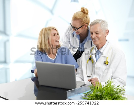 Portrait of three doctors working on laptop., while sitting at desk at private clinic.