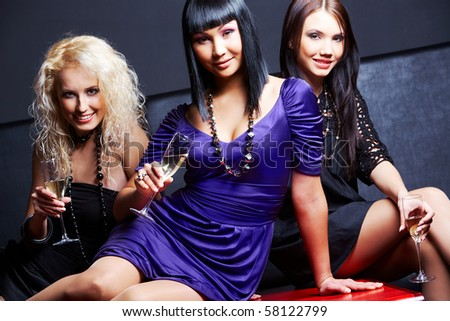 Portrait of three fashionable young women with flutes looking at camera