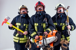 Portrait of three firefighters standing together white background studio