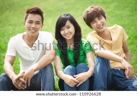 Portrait of three friends sitting on the grass