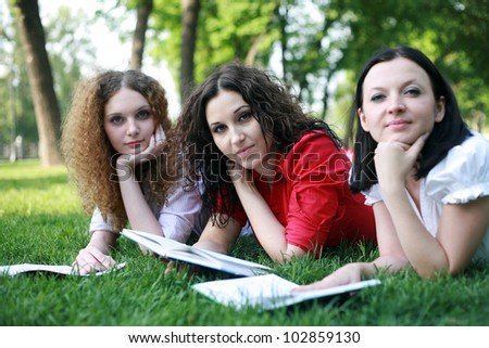 Portrait of three friends studying on the grass in the park
