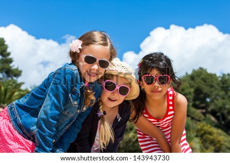 Portrait of three friends together wearing sunglasses outdoors.