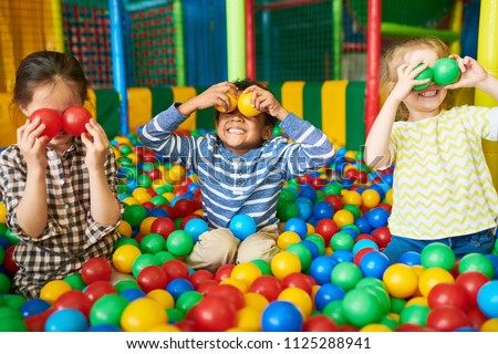 Portrait of three funny little kids playing in ball pit and enjoying time in childrens entertainment and play area, copy space #1125288941