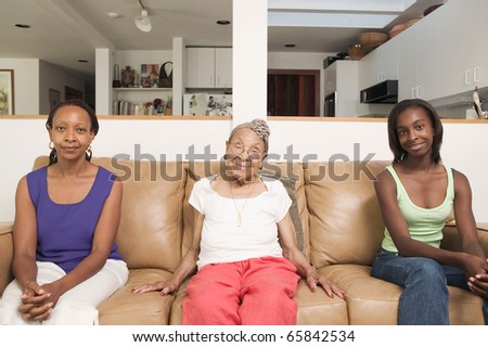 Portrait of three generations of women sitting on couch