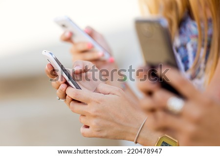 Portrait of three girls chatting with their smartphones at the park