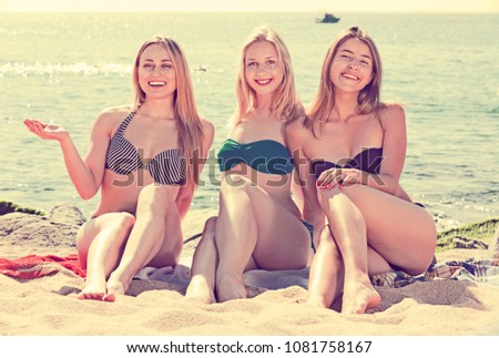 0652db902e9 Portrait of three happy charming young women in swimsuits resting ...