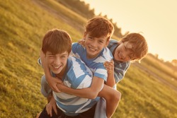 Portrait of three happy cheerful brothers at sunset, outdoor