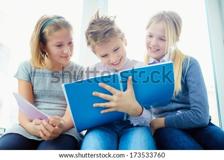 Portrait of three happy classmates looking at notes in exercise book of schoolboy while he writing