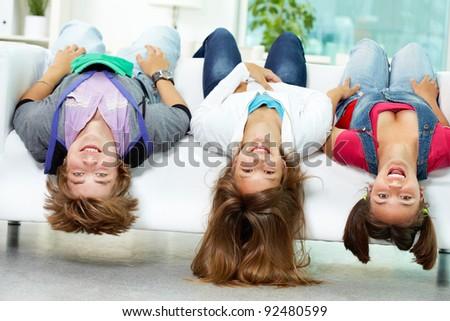 Portrait of three happy friends having fun on sofa - stock photo
