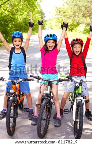 Portrait of three happy little cyclists