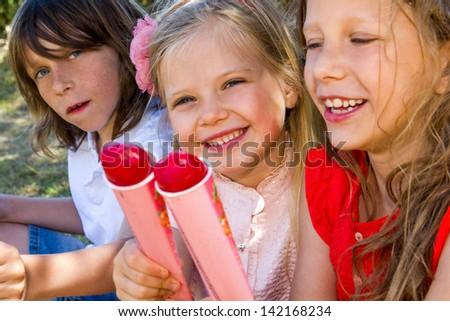 Portrait of three kids enjoying ice pops outdoors.
