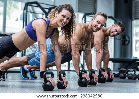 Portrait of three muscular athletes on a plank position