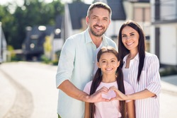Portrait of three nice lovely cheerful affectionate people dad mom teen daughter embracing showing heart shape outside sunny day