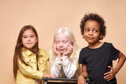 portrait of three shy and calm diverse kids isolated in studio. albino girl with white skin and hair color stand bored, her africanamerican and european friends stand next to her