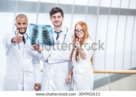 Portrait of three smiling doctors. Three confident doctor holding x-ray of lungs in his hands and looking with a smile at the camera and show a thumbs up
