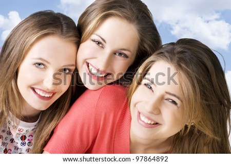 Portrait of three young beautiful  happy girls over sky background