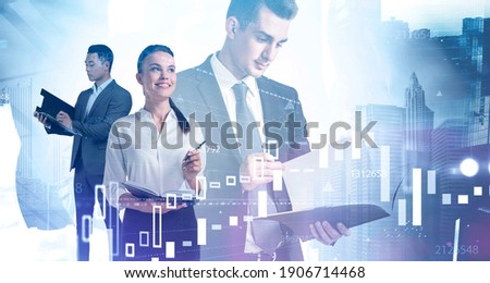 Portrait of three young diverse business people working together in blurry abstract city with double exposure of financial charts. Toned image