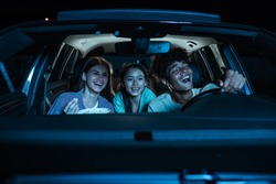Portrait of three young friends looking emotional, laughing while sitting together in the car and watching a movie in a drive in cinema. Entertainment, leisure activities concept. Horizontal shot