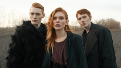Portrait of three young redhead models. Freckles. Beautiful faces. Unusual clothes. Nature background. North. Siberia. Scandinavian culture. Autumn. Grey field. Clouds. Medieval style. Fashion