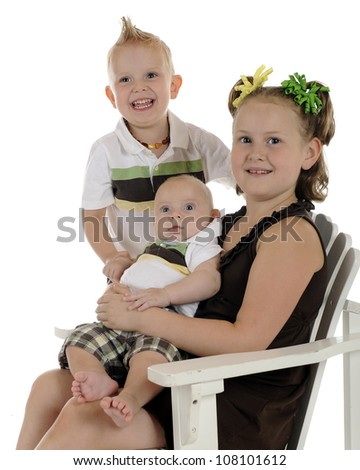 Portrait of three young siblings with focus on baby.  On a white background.