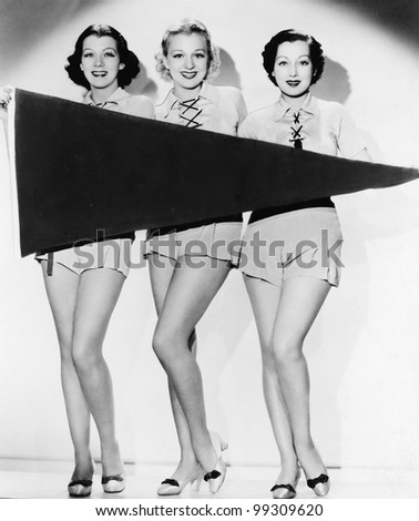Portrait of three young women holding a banner and smiling Zdjęcia stock ©