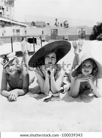 Portrait of three young women lying on the beach