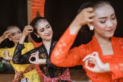 portrait of three young women presenting traditional Javanese dance movements